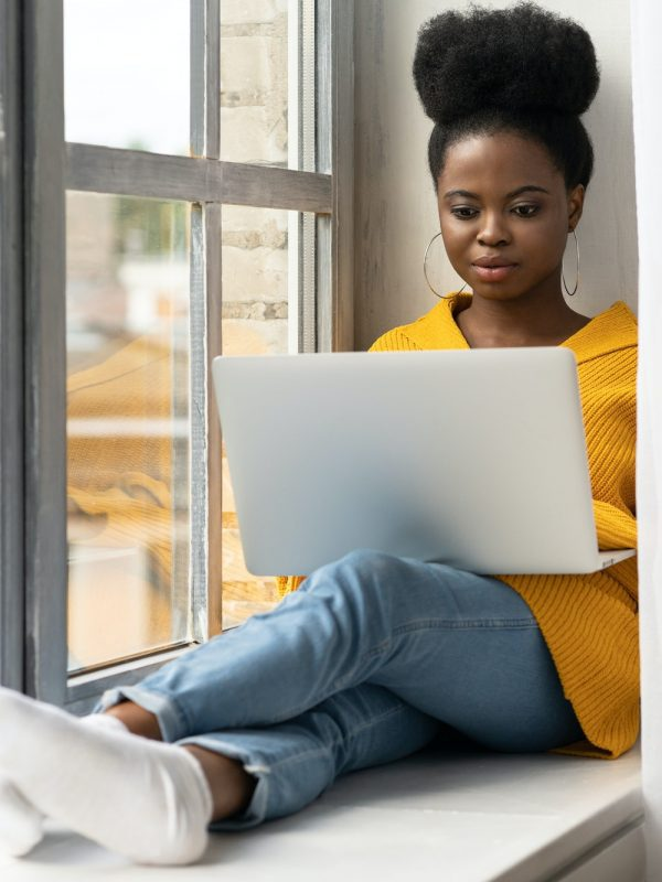 Black woman sitting on windowsill, working on laptop, distance online learning preparing for an exam